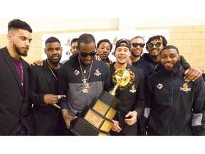 Kirk Williams Jr. of the Lightning holds the league championship trophy surrounded by teammates Julian Boyd, left, Kyle Johnson, Yohanny Dalembert, Marcus Capers, Joel Friesen-Latty, Garrett Williamson, Mo Bolden and Ashton Smith during a meet and greet with their fans at their Blackfriars Road gym. The Lightning came back from a 2-0 deficit to win 4-3 over the Halifax Hurricanes for their fourth league championship, and on Tuesday they celebrated with an open house for their fans.  Mike Hensen/The London Free Press