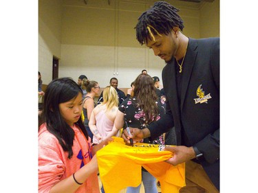 Six-foot-10 Lightning forward Mo Bolden signs a t-shirt for Lily Wright, 12, during a meet and greet with fans at the Lightnings' Blackfriars Road gym. The Lightning came back from a 2-0 deficit to win 4-3 over the Halifax Hurricanes for their fourth league championship, and on Tuesday they celebrated with an open house for their fans.  Mike Hensen/The London Free Press
