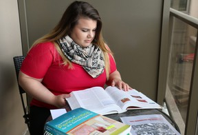 Dental hygiene student Merisa Buragina reviews one of her textbooks on her apartment's balcony. Buragina will graduate from her program on June 7. (SHANNON COULTER, The London Free Press)