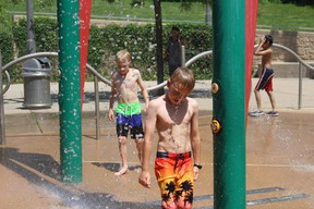 Michael, left, 11, and Will Johnston, 9, cool off in the spray pad at the forks of the Thames River near Ivey Park on Friday. (Shalu Mehta, London Free Press)