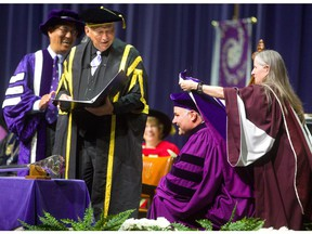 All 6 feet 4 inches of Eric Lindros has to kneel on stage at Alumni Hall to be hooded for his honorary doctorate on Monday, giving Western University president Amit Chakma, left, and chancellor Jack Cowin a good laugh. Mike Hensen/The London Free Press.