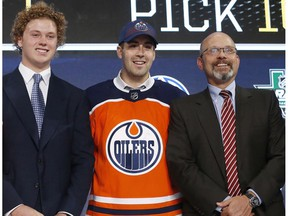 Evan Bouchard, center, of Canada, poses after being selected by the Edmonton Oilers during the NHL hockey draft in Dallas, Friday, June 22, 2018.