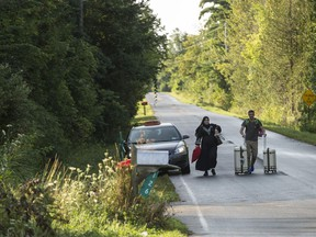 A cab drops off a couple of asylum seekers at the US/Canada border near Champlain, New York. Thousands of refugees streamed across the Canada/US, overwhelming the government's capacity to house them while their claims are processed.
