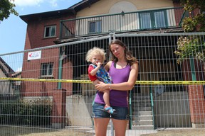 Eva Neudorf stands in front of her home with her one-year-old son Gavin. Her unit, as well as three others that are part of Tolpuddle Housing Co-op, were totally lost after a fire erupted Sunday night. A total of 12 families are currently displaced from the building. (SHALU MEHTA, The London Free Press)