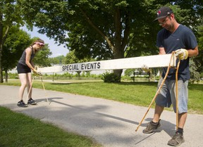 Sam Taylor, left and Lawrence Field both of London dismantle the barricades in Harris Park the day after the Canada Day celebrations in London, Ont.  The two work for Admiral Live who were contracted by the city to run the events on Canada Day. (Mike Hensen/The London Free Press)