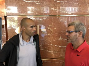 Decathlete Damian Warner chats with coach Gar Leyshon at a news conference at One London Place Friday to announce that Warner is returning to London to train. (Paul Vanderhoeven/The London Free Press)
