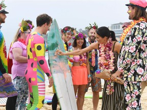 Tecumseh's Mark Micelli, left, in the bright body suit, holds a board as the Duchess of Sussex applies surfing wax during a visit by Prince Harry and his wife with members of a local surfing community group at Bondi Beach in Sydney on Oct. 19, 2018, during their Australian tour.