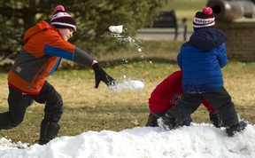 Even though there's not much snow in London this Christmas, the Popescu brothers found enough in Victoria Park for a fraternal snowball fight. Paul, 9 (in orange) was trying to get his little brother Patrick, 5,(Blue) who was in turn trying to hide behind Paul's twin, Peter, (red) with little success. The snow was made up of the scrapings off the skating rink, so it didn't make the best snowballs, but that wasn't enough to slow them down. (Mike Hensen/The London Free Press)