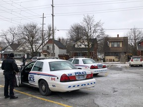 Two London police officers exit their cruisers near the scene of a shooting in the area of Florence Street and Kellogg Lane, just east of the Western Fair Sports Centre. A man suffered several gunshot wounds, police say. Photo taken Monday Feb. 25, 2019. (JONATHAN JUHA, The London Free Press)
