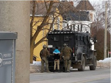 Police officers escort a handcuffed suspect to vehicle after a nearly nine-hour standoff on Main Street in Listowel. (Crystal Kaiser/Special to the Beacon Herald)