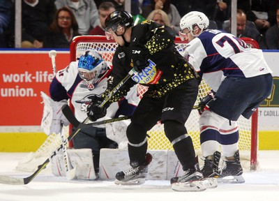 Robert Thomas of the Knights tries to jam a rebound past Michael DiPietro of the Spitfires while being checked by Sean Day in the first period of their Friday night game at Budweiser Gardens.  Mike Hensen/The London Free Press/Postmedia Network (2017)