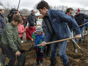 Prime Minister Justin Trudeau fills sandbags with his son Xavier, as son Hadrien watches, in Constance Bay on Saturday.