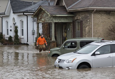 About 5,000 people were evacuated from their homes in Brantford on Wednesday when the city declared a state of emergency due to flooding from the Grand River.  A man walks through the flood waters at Grand River Street and Scarfe Avenue.   Brian Thompson/Postmedia Network ORG XMIT: POS1802211119297072