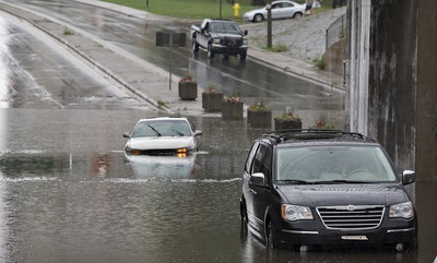 A heavy downpour just before 7:00 p.m. on Sunday June 14, 2015 flooded many underpasses in Brantford, Ontario including here at St. Paul Avenue near Brant Avenue.  The road was closed while vehicles were towed out and until water levels drained. Brian Thompson/Brantford Expositor/Postmedia Network