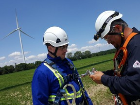 Kevin Aikenhead, left, facility manager for South Kent Wind, and Jamie Edwards, lead technician, prepare their safety harnesses at the wind farm, located southwest of Chatham. The 124-turbine project, owned by Pattern Energy and Samsung, became operational in 2014. (Trevor Terfloth/The Daily News)