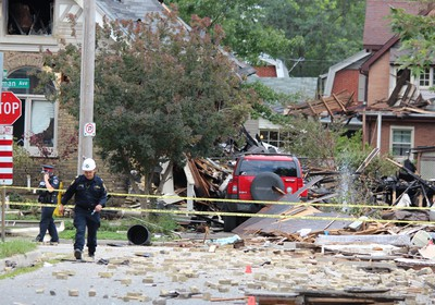 Emergency crews remained on the scene Thursday, Aug. 15, 2019, at Woodman Avenue, where a vehicle crashed into a home, causing an explosion that injured seven and damaged at least 10 homes. DALE CARRUTHERS / THE LONDON FREE PRESS