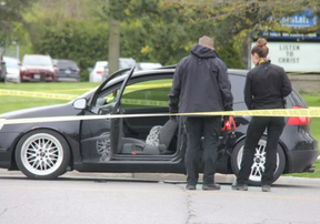 London police officers inspect a vehicle at the scene of a shooting at the corner of Trafalgar Street and Admiral Drive. Photo taken May 11, 2019.