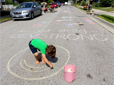 Four-year-old Bram Davis fills in a happy face on Woodman Avenue, just a few homes north of the natural gas explosion site in Old East Village in London, Ont.  Behind Davis is the slogan,