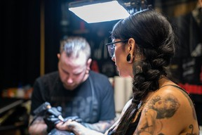 Jessie Lee, of Hollywood, California, gets a Tim Horton's cup tattoo from Will Smink, owner of London's Ink by Smink Tattoos, at the Inked Circus Tattoo Expo Sunday. (MAX MARTIN, The London Free Press)