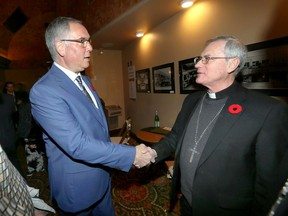 Catholic church abuse survivor Pat McMahon, left, greets Bishop Ronald Fabbro during the opening night of the film PREY at Capitol Theatre Wednesday.