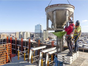 Anthony Soboczynski and Jordan Sargent of Ellis-Don handle a two-cubic-yard bucket as they pour concrete through a large funnel on Friday to fill one of eight support pillars that will hold up the new Old Oak apartment building being built at 515 Richmond St. across from St. Peter's Basilica. More Londoners are working, according to Statistics Canada October figures. (Mike Hensen/The London Free Press)