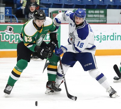 Owen Robinson, right, of the Sudbury Wolves, and Hunter Skinner, of the London Knights, battle for the puck during OHL action at the Sudbury Community Arena in Sudbury, Ont. on Friday December 20, 2019. John Lappa/Sudbury Star/Postmedia Network