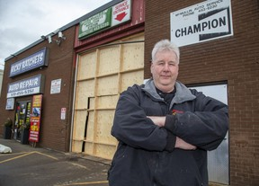 Rick McMullin, owner of Ricky Ratchets Auto Repair, has had to erect a temporary wood door after a truck recently crashed through the bay door in London. Derek Ruttan/The London Free Press/Postmedia Network