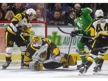 Alec Regula of the Knights gets a slashing penalty digging for the puck under Hamilton goalie Zachary Roy as the London Knights host the Hamilton Bulldogs at Budweiser Gardens on Friday Jan. 24, 2020.   (Mike Hensen/The London Free Press)