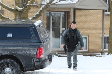 A London police officer leaves an apartment at 63 Wellington Rd., where city police assisted their Brantford counterparts in arresting homicide suspect Shajjad Hossain Idrish, 22, on Friday. DALE CARRUTHERS / THE LONDON FREE PRESS