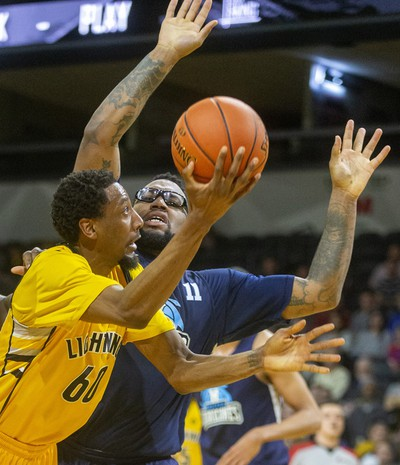 Marcus Capers of the London Lightning tries for a shot as he's knocked to the court by Halifax's Carl Hal during their Sunday afternoon game at Budweiser Gardens in London. Photograph taken on Sunday February 9, 2020.  Mike Hensen/The London Free Press/Postmedia Network