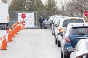 Nine cars were lined up at the 11 a.m. opening of the Oakridge Arena COVID-19 assessment centre in London, Ont. on Sunday March 29, 2020. Derek Ruttan/The London Free Press/Postmedia Network
