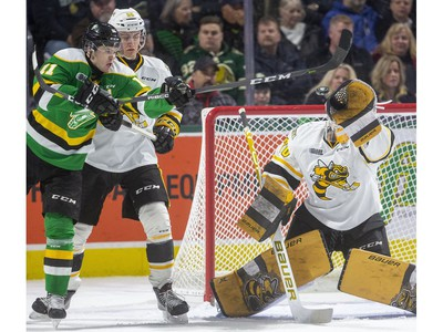 Knights forward Connor McMichael lunges to try to deflect a high shot past Sting goalie Benjamin Gaudreau while being checked by Eric Hjorth during the first period of their OHL game  Friday March 6, 2020, at Budweiser Gardens. Mike Hensen/The London Free Press