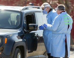 Health workers screen motorists for the possible symptoms of COVID-19 on Wednesday outside at the Carling Heights Optimist Centre, one of two screening centres set up in London. (Mike Hensen/The London Free Press)
