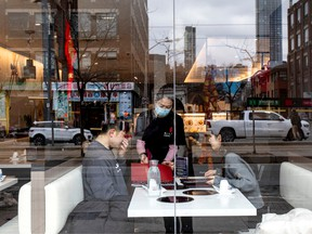 A server attends to customers at a restaurant in the Chinatown district of Toronto in late January. Asian restaurants in Canada have already seen a drop in sales.