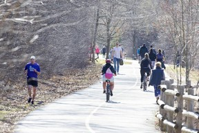 People keep their distance while walking, running and biking beside the Thames River at near Springbank Park in London. (Derek Ruttan/The London Free Press)