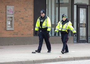 Police constables walk east Dundas Street just past Lyle Street in London, Ont. on Tuesday April 14, 2020. (Derek Ruttan/The London Free Press)