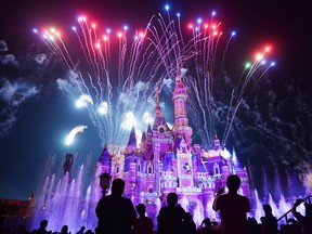 This photo taken on June 16, 2017, shows visitors watching fireworks exploding over the castle at an event to mark the first anniversary of the opening of Shanghai Disneyland, in Shanghai.