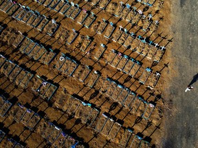 Aerial view showing a man walking past graves in the Nossa Senhora Aparecida cemetery in Manaus on June 21, 2020. - The novel coronavirus has killed at least 464,423 people worldwide since the outbreak began in China last December, being Brazil Latin America's worsthit country with 49,976 deaths from 1,067,579 cases.