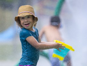 Kaya Shepard, 4, of London, takes her bucket to be filled at the Gibbons Park splash pad. (Mike Hensen/The London Free Press)