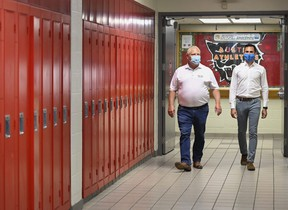 Ontario Premier Doug Ford, left, and Education Minister Stephen Lecce walk the hallway before making an announcement regarding the governments plan for a safe reopening of schools in the fall due to the COVID-19 pandemic at Father Leo J Austin Catholic Secondary School in Whitby, Ont., on Thursday, July 30, 2020.
