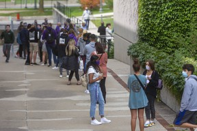 A long line of Western  University students waits to be assessed at the on-campus COVID-19 assessment centre, which opened at 11 a.m. Monday. By noon, officials said it had reached its daily capacity of 220 tests. Many of those left waiting were given a red ticket to come back at another time Monday, or told to return Tuesday. (Mike Hensen/The London Free Press)