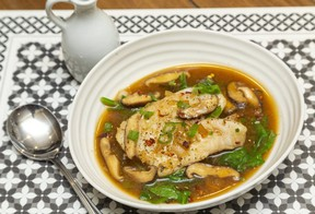Poached cod with a rich broth garnished with spinach and green onion makes a delicious transition to fall cuisine, says food columnist Jill Wilcox. (Mike Hensen/The London Free Press)