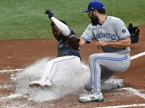 Rays outfielder Randy Arozarena (left) slides into home plate as Blue Jays pitcher Robby Ray (right) attempts to catch the ball in the fourth inning at Tropicana Field, in St. Petersburg, Fla., Tuesday, Sept 29, 2020.