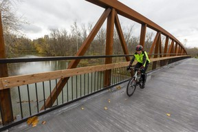 """Jiri Svoboda rides his bike over the new bridge near Adelaide Street connecting sections of London's Thames Valley Trail Friday. """"Honestly, I've been coming past here all summer waiting for this,"""" said Svoboda, who has cycled 10,000 kms this year.   (Mike Hensen/The London Free Press)"""