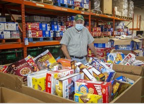 Glen Pearson, co-executive director of the London Food Bank, helps sort donations for the agency's Thanksgiving food drive Tuesday. Derek Ruttan/The London Free Press