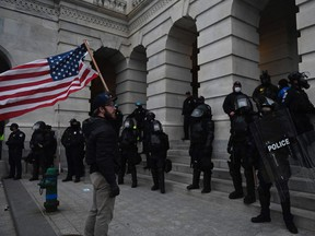 A Trump supporter confronts police and security forces at the US Capitol in Washington, DC, on January 6, 2021. - Demonstrators breeched security and entered the Capitol as Congress debated the a 2020 presidential election Electoral Vote Certification. (Photo by ANDREW CABALLERO-REYNOLDS / AFP)