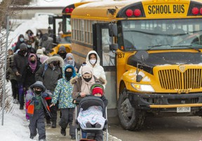 Students and parents file past buses that some students use to get home, while others walk with their parents as they left Eagle Heights public school for the walk home after the first day of in class schooling this year in London, Ont. (Mike Hensen/The London Free Press)