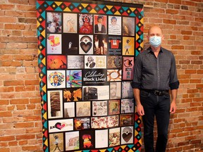 Thames Art Gallery curator Phil Vanderwall displays the Celebrating Black Lives: Community Quilt Project, comprising of artwork by 35 participants. The quilt is on public display at ARTspace's Window Gallery throughout Black History Month. (Ellwood Shreve/Chatham Daily News)