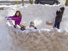 Kaida Savard, age 10 (left), her six-year-old sister Kalia and friend Riley Ferguson-Law, 6 place chunks of snow on a large snow fort encompassing the entire front yard of a Chatham Street home on Saturday February 20, 2021 in Brantford, Ontario. EDS NOTE: The child at far right could not have her name used as per the parent's request.