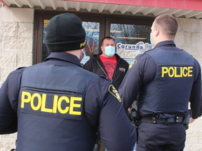 Ron Theriault, owner of Corunna Fitness Centre, speaks Monday with OPP officers outside his gym on Hill Street in Corunna. The OPP officers warned Theriault that he was violating provincial lockdown rules by keeping his gym open. (Paul Morden, Postmedia Network)
